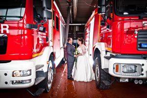 Brautpaar Sandra zwischen großen Feuerwehr Autos